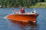 Man riding a classic wooden boat