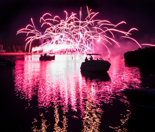 Photo of colorful, exploding fireworks in the night sky during a July 4th holiday celebration in Toledo Ohio Taken  along the Maumee river with boats and colorful reflections in the water.